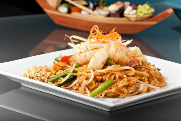 Seafood pad Thai dish of stir fried rice noodles on a square white plate with chopsticks and grated carrot garnish.